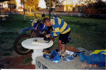 George servicing his bike at Kulgera.