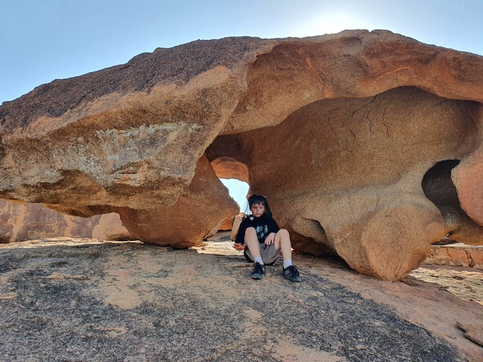 Logan is sitting under an spectacularly eroded rock. The rock has aboriginal artwork on the roof.