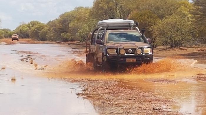Matt in his Navara tows the trailer through the creek.