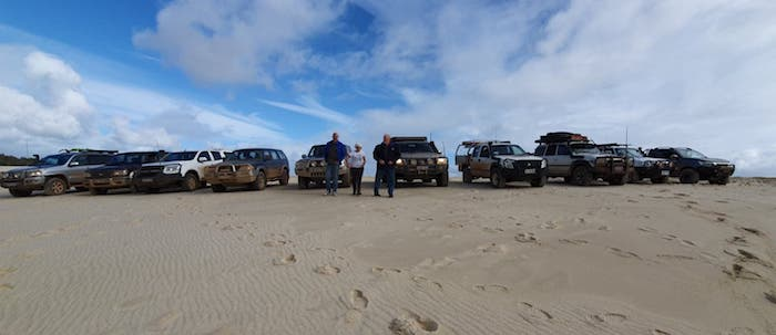 Vehicle lineup on top of first dune.