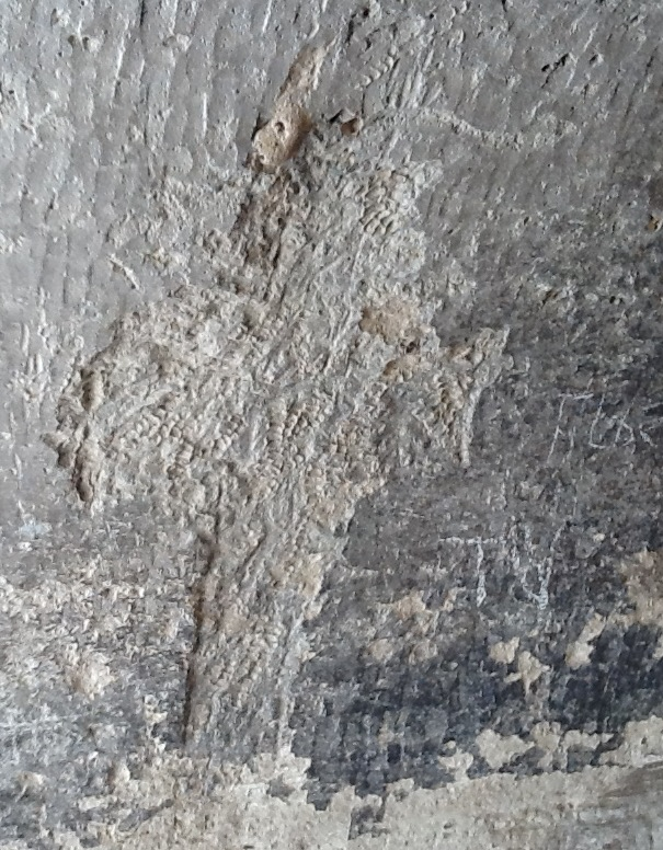 A cross in relief on the wall of the cave.