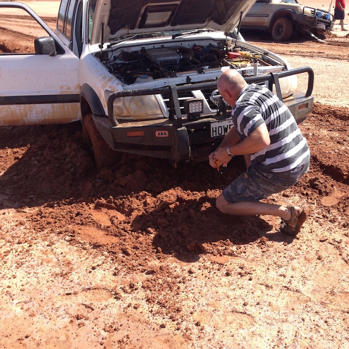 Graham removing mud to get MaxTrax under the wheel.